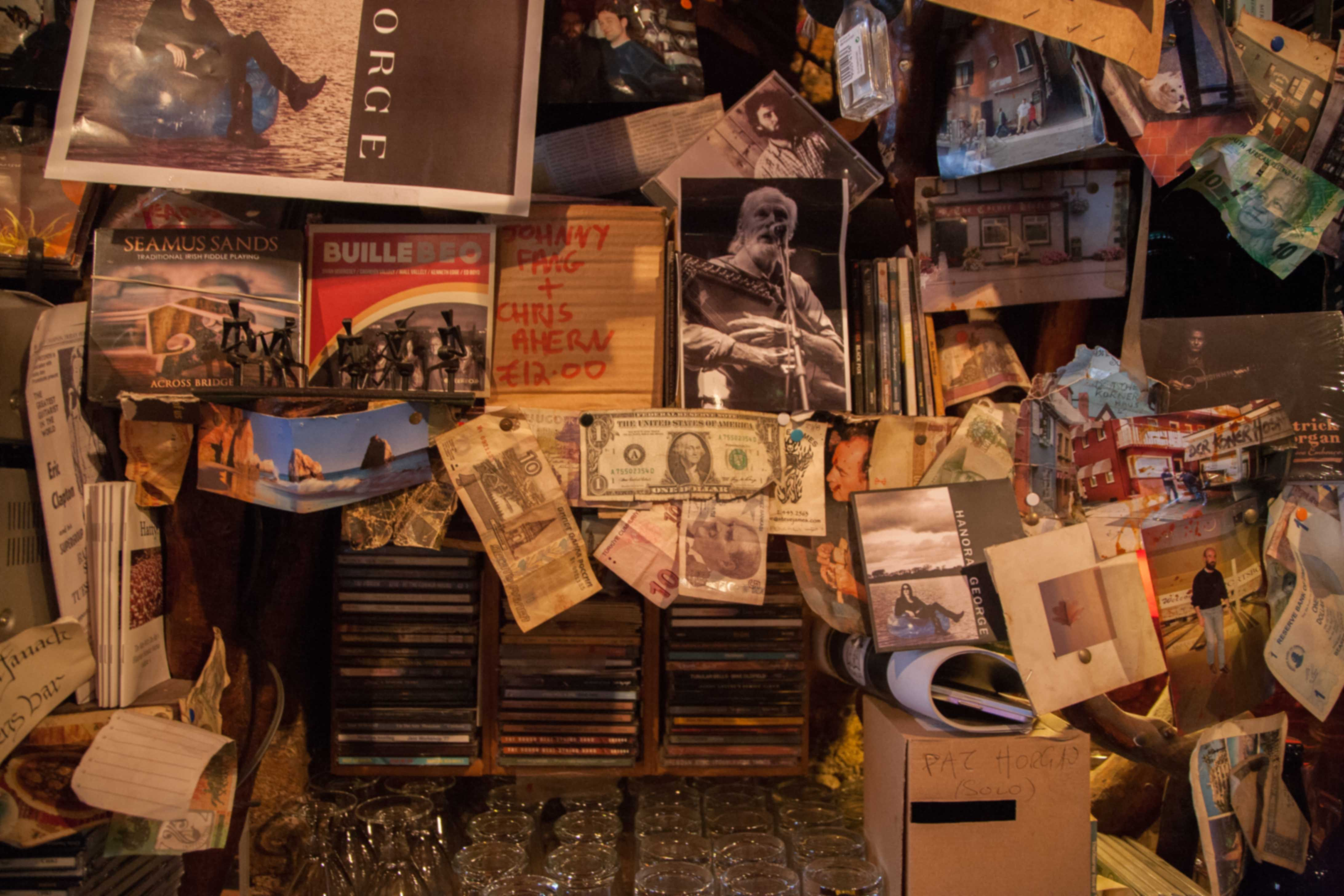 Music cd's and clutter behind the bar of a traditional pub