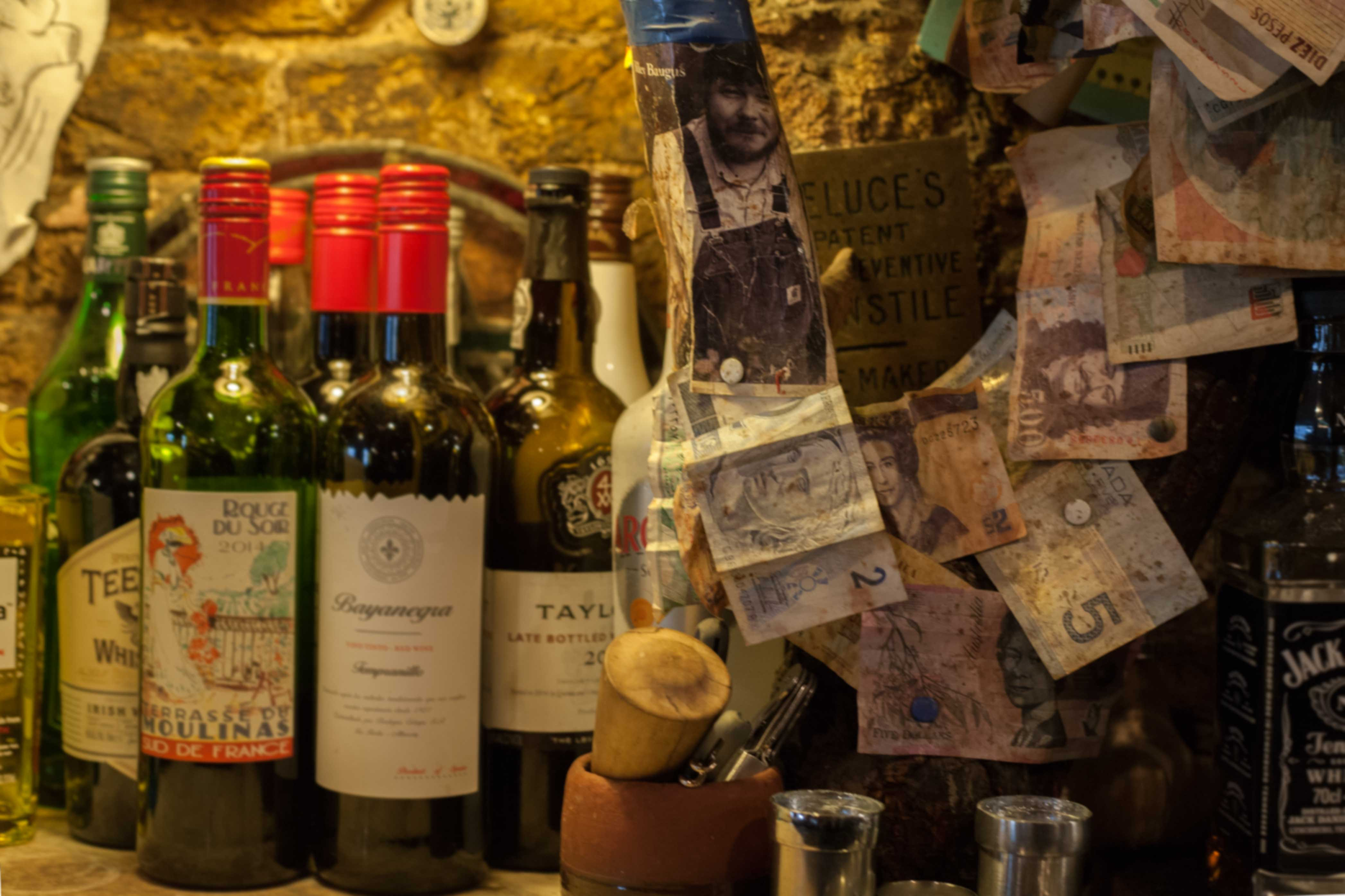 Wine bottles and clutter behind the bar of a traditional pub in Cork